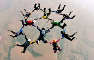 Skydivers,Holding,Hands,Making,A,Fomation.,High,Angle,View.